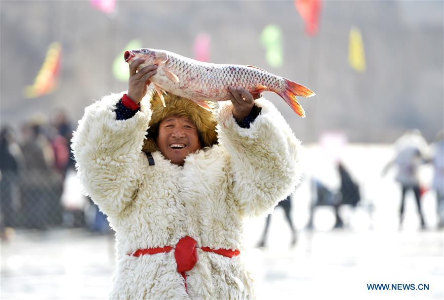 An Inheritor of Chagan Lake winter fishing heritage shows a fish just caught in Qianyaozi Reservoir in Hohhot, capital of north China\'s Inner Mongolia Autonomous Region, Jan. 26, 2019. A two-day winter fishing tourism festival opened here on Saturday, during which 18 inheritors of Chagan Lake winter fishing showed visitors traditional ways of fishing. Winter fishing on ice-covered Chagan Lake dates back to the Liao and Jin dynasties from 10th century to the 13th century in China and was listed into the national intangible cultural heritage in 2008. (Xinhua/Wang Zheng)