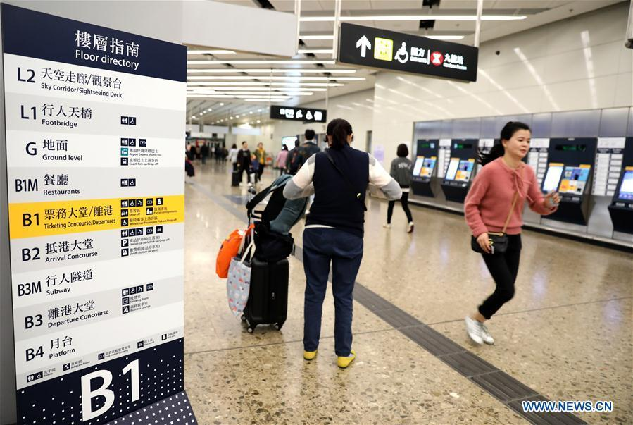 Passengers walk at the West Kowloon railway station in Hong Kong, south China, Jan. 25, 2019. To better serve the passengers using the automotive ticket machines, blue signs are installed and staff members in orange are dispatched to offer help at the West Kowloon railway station in Hong Kong. (Xinhua/Wu Xiaochu)