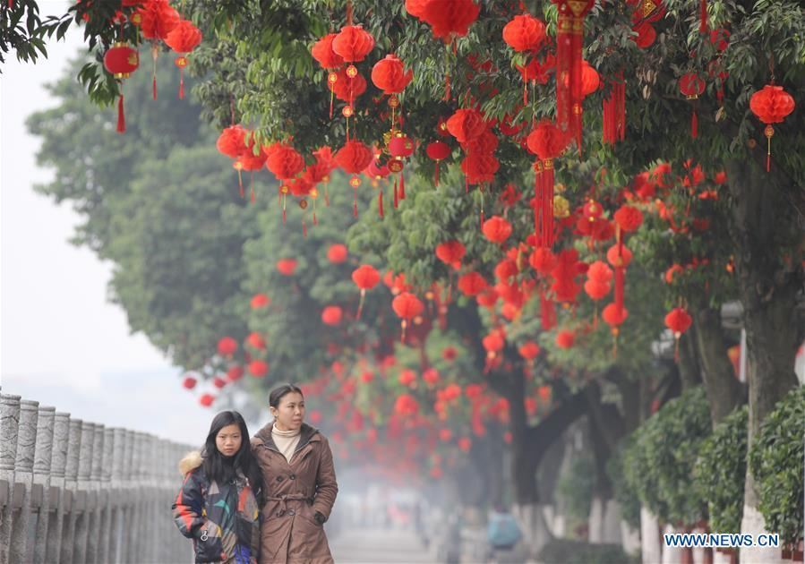 People walk past red decorations on a road in Daoxian County, Yongzhou of central China\'s Hunan Province, Jan. 26, 2019. Red decorations are arranged across China to greet the upcoming lunar New Year which will fall on Feb. 5 this year. (Xinhua/He Hongfu)