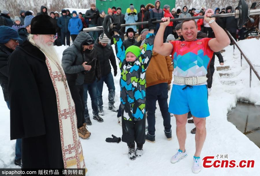 A Russian Orthodox clergeman (L) and bodybuilder Yuri Golubev (R front) before a world record attempt by Andrei Lobkov (not in picture) for the most consecutive bench presses in 1 minute while standing in an ice hole, in the frozen Moskva River in north-west Moscow; the record attempt is dedicated to John the Baptist.  (Photo/Sipaphoto.com)