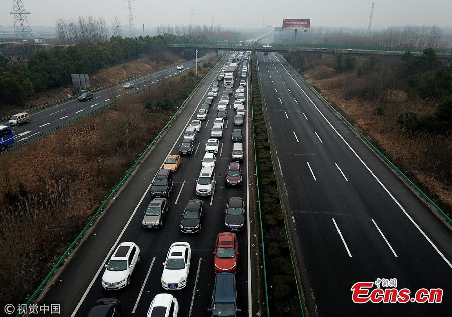An aerial photo shows heavy traffic heading in one direction on an expressway while, in comparison, the opposite side of the road remains almost empty in Anhui Province. China is in the midst of its Spring Festival travel rush as millions of people go home for family reunions for the most important festival of the year. (Photo/VCG)