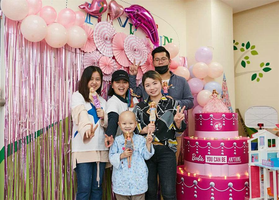 Volunteers and Xinyi take a group picture in the ward decorated to a Barbie theme at Shanghai Xinhua Hospital. (Photo provided to chinadaily.com.cn)