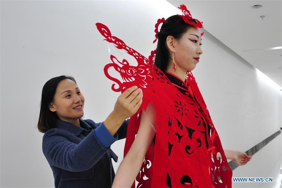 Craftswoman Liang Ying (L) helps a cheongsam enthusiast put on her papercutting work of cheongsam at her studio in Liaocheng, east China\'s Shandong Province, Jan. 30, 2019. Liang Ying made 18 papercutting works of cheongsam to greet the upcoming Spring Festival, which falls on Feb. 5 this year. (Xinhua/Xu Wenhao)