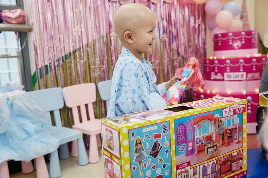 Xinyi enjoys her time with Barbie dolls, changing their clothes, combing their hair, and making afternoon tea for her new friends. (Photo provided to chinadaily.com.cn)  A six-year-old girl fighting a high-risk cancer has fulfilled her dream of hosting a party with Barbie dolls in Shanghai.  The girl, identified by her given name Xinyi, is undergoing treatment for neuroblastoma, a type of cancer that forms in certain types of nerve tissue.  On Jan 29, she got to spend a day in her room at Shanghai Xinhua Hospital with the ward decorated all to the theme of Barbie.  Supported by volunteers from nonprofit charity organization Make-A-Wish Shanghai and US multinational toy manufacturing company Mattel, the girl played house and had fun with her favorite dolls.  \