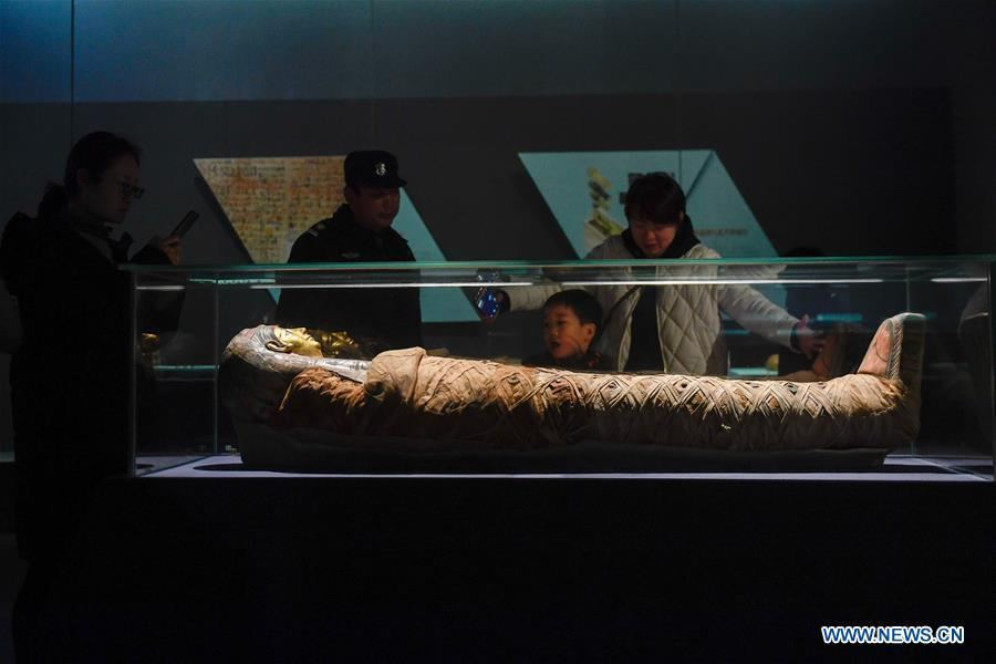 People look at a mummy displayed in an exhibition of ancient Egyptian civilization at Zhejiang West Lake Gallery in Hangzhou, capital of east China\'s Zhejiang Province, Jan. 30, 2019. A total of 180 cultural relics from Italian museums are displayed in an exhibition of ancient Egyptian civilization from Jan. 22 to May 5, 2019. (Xinhua/Huang Zongzhi)