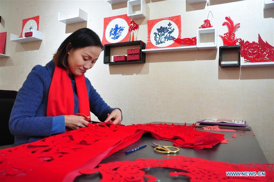 Craftswoman Liang Ying creates papercutting works of cheongsam at her studio in Liaocheng, east China\'s Shandong Province, Jan. 30, 2019. Liang Ying made 18 papercutting works of cheongsam to greet the upcoming Spring Festival, which falls on Feb. 5 this year. (Xinhua/Xu Wenhao)