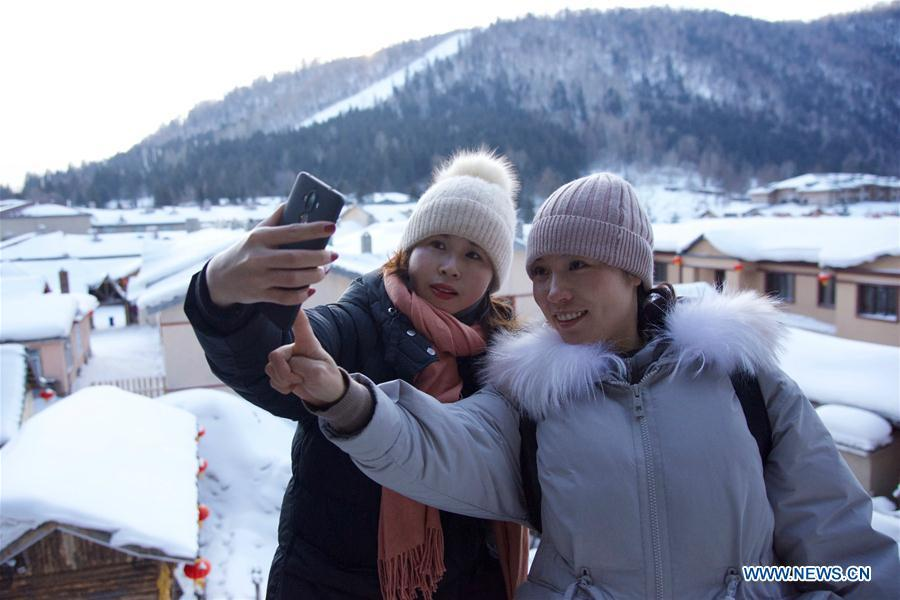Tourists take selfie at the snow-covered Shuangfeng Forest Farm in Mudanjiang City, northeast China\'s Heilongjiang Province, Jan. 31, 2019. The Shuangfeng Forest Farm witnesses frequent snowfalls and is covered with snow for most of the year. The beautiful snow scenery here attracts many visitors from at home and abroad every year. (Xinhua/Yang Siqi)