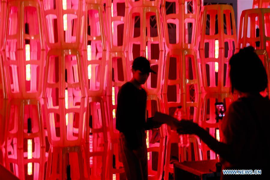 A visitor poses for a photo amid a light installation during the Bangkok Design Week 2019 in Bangkok, Thailand, Jan. 30, 2019. The Bangkok Design Week 2019 was held under the theme \