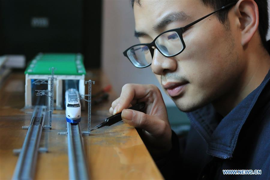 Zhang Yuqi makes a model of a bullet train maintenance center at his home in Guiyang, capital of southwest China\'s Guizhou Province, Jan. 30, 2019. As a model train hobbyist, 27-year-old Zhang Yuqi has made and collected more than a hundred model trains. Zhang is also a bullet train mechanic responsible for checking bullet trains during the Spring Festival travel rush at a maintenance center in Guiyang of Guizhou Province. Despite heavy work load and work pressure, Zhang said he is dedicated to ensuring the safety of bullet trains. (Xinhua/Ou Dongqu)