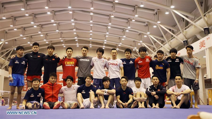 Members of Chinese and Japanese men\'s gymnastics teams pose for a group photo after a training in Beijing, capital of China, Jan. 30, 2019. First-ever China-Japan gymnastics co-training camp started here on Jan. 27. (Xinhua/Luo Yuan)