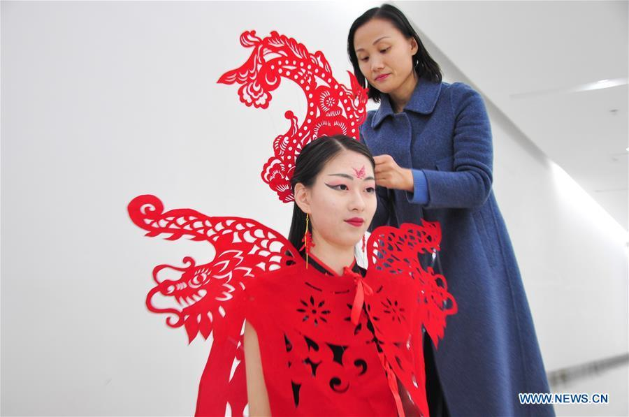 Craftswoman Liang Ying (R) helps a cheongsam enthusiast put on her papercutting work of cheongsam at her studio in Liaocheng, east China\'s Shandong Province, Jan. 30, 2019. Liang Ying made 18 papercutting works of cheongsam to greet the upcoming Spring Festival, which falls on Feb. 5 this year. (Xinhua/Xu Wenhao)