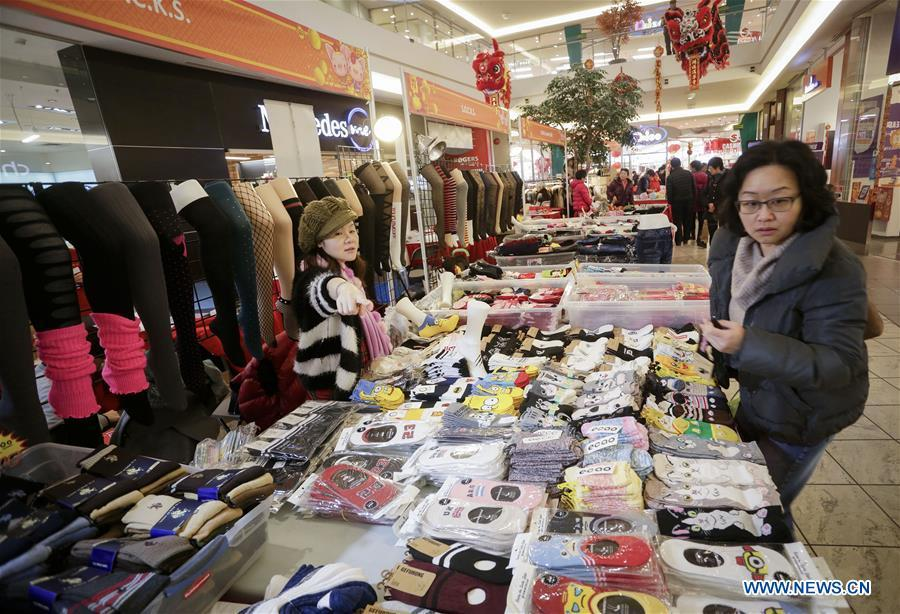 A resident shops for socks while visiting the 30th Chinese Lunar New Year Flower & Gift Fair in Richmond, Canada, Jan. 30, 2019. The seven-day Chinese Lunar New Year Flower & Gift Fair, west Canada\'s largest indoor Lunar New Year festivity, was opened on Tuesday. (Xinhua /Liang Sen)
