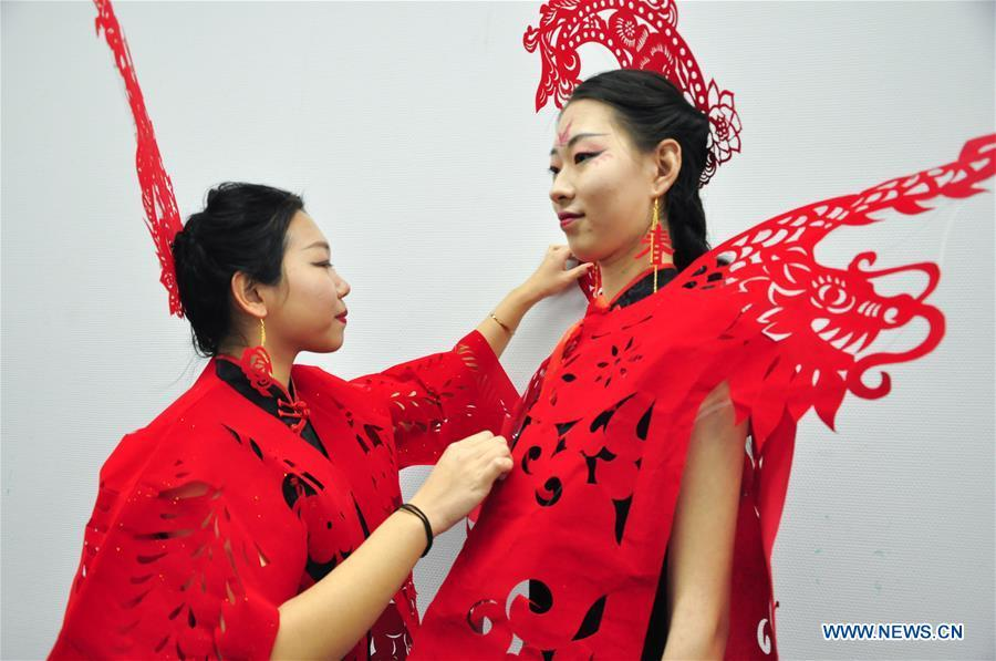 Cheongsam enthusiasts arrange papercutting works of cheongsam made by craftswoman Liang Ying at her studio in Liaocheng, east China\'s Shandong Province, Jan. 30, 2019. Liang Ying made 18 papercutting works of cheongsam to greet the upcoming Spring Festival, which falls on Feb. 5 this year. (Xinhua/Xu Wenhao)