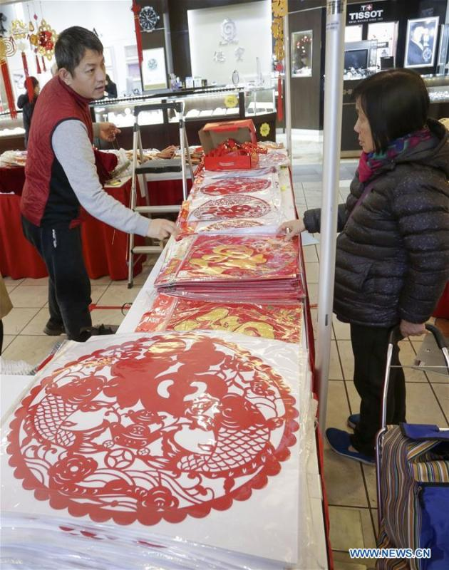 A resident selects paper decorations during the 30th Chinese Lunar New Year Flower & Gift Fair in Richmond, Canada, Jan. 30, 2019. The seven-day Chinese Lunar New Year Flower & Gift Fair, west Canada\'s largest indoor Lunar New Year festivity, was opened on Tuesday. (Xinhua /Liang Sen)