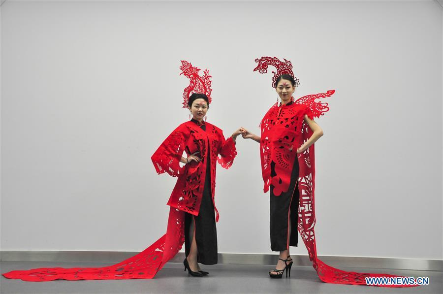 Cheongsam enthusiasts display papercutting works of cheongsam made by craftswoman Liang Ying at her studio in Liaocheng, east China\'s Shandong Province, Jan. 30, 2019. Liang Ying made 18 papercutting works of cheongsam to greet the upcoming Spring Festival, which falls on Feb. 5 this year. (Xinhua/Xu Wenhao)