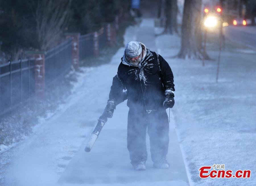 James Dusenbery blows a dusting snow off the sidewalk in Englewood, N.J., Jan. 30, 2019. The National Weather Service issued blizzard warnings for sections of upstate New York on Wednesday and officials urged people to stay inside as heavy, wind-driven snow caused whiteout conditions amid subzero windchills. (Photo/Agencies)