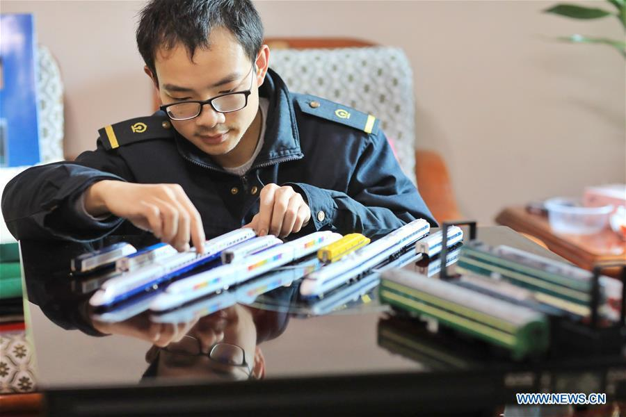 Zhang Yuqi makes model trains at his home in Guiyang, capital of southwest China\'s Guizhou Province, Jan. 30, 2019. As a model train hobbyist, 27-year-old Zhang Yuqi has made and collected more than a hundred model trains. Zhang is also a bullet train mechanic responsible for checking bullet trains during the Spring Festival travel rush at a maintenance center in Guiyang of Guizhou Province. Despite heavy work load and work pressure, Zhang said he is dedicated to ensuring the safety of bullet trains. (Xinhua/Ou Dongqu)