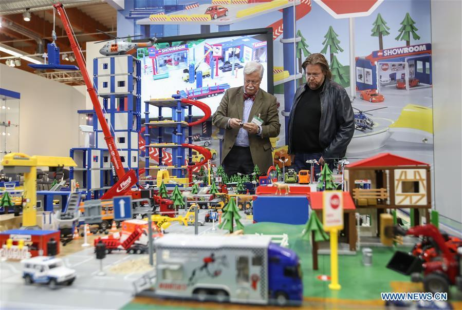 Two visitors view products at the booth of Siku in the Spielwarenmesse exhibition in Nuremberg, Germany, Jan. 30, 2019. Spielwarenmesse, a leading international fair for toys, hobbies and leisure, kicked off in Nuremberg on Wednesday. Around 2,900 manufacturers from all over the world gathered at the annual trade fair, which will last until Feb. 3 and is expected to attract 71,000 visitors from over 125 nations and regions. (Xinhua/Shan Yuqi)