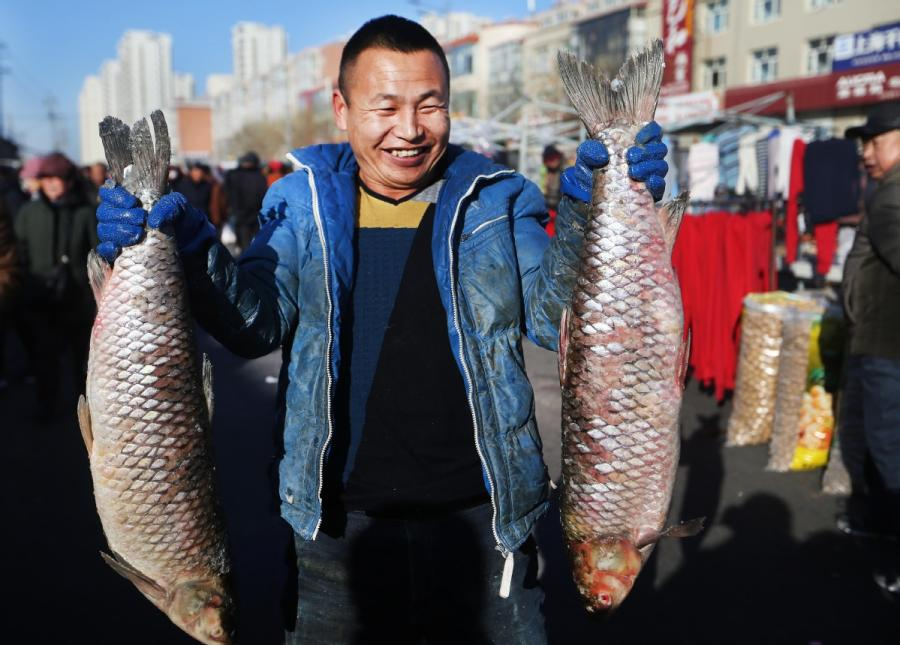 A fisherman catches two fish before selling them at a market in Yanqing district, Beijing. (Photo by Tian Baoxi/Provided to chinadaily.com.cn)  Fishing season has opened on Yeya Lake in Yanqing, Beijing\'s northwestern district, with villagers catching the first haul of fish in celebration of the upcoming Spring Festival.  On the 1,300-hectare lake of Heimuwa village, fishermen are out trying to catch fish. Liu Changhai, who caught almost 300 kilos of fish in significant haul, said he is excited for the harvest. \