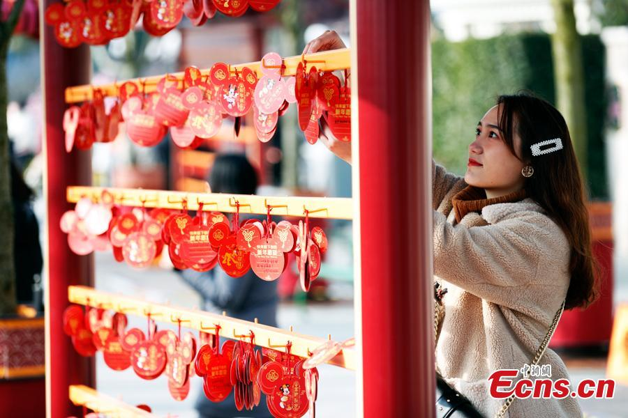 A visitor puts up her wish card in the Shanghai Disney Resort to greet \