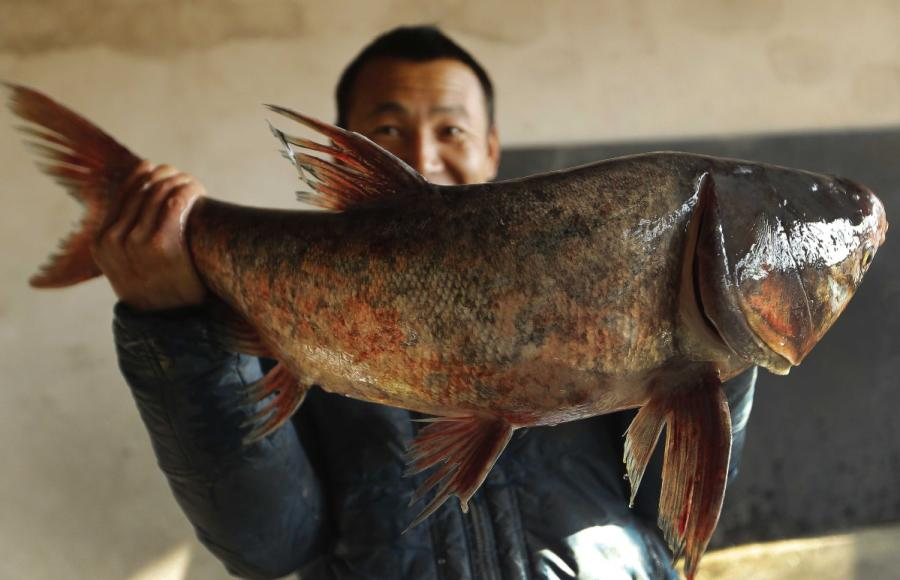 A man shows off a fish he caught from Yeya Lake. (Photo by Tian Baoxi/Provided to chinadaily.com.cn)