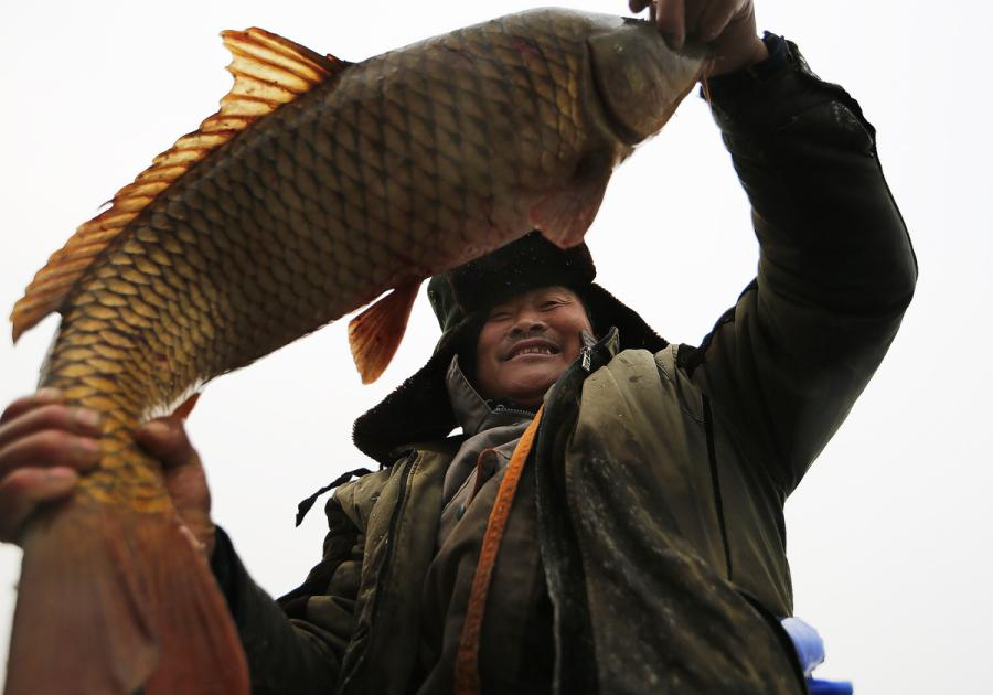 A man shows off the fish he caught from Yeya Lake. (Photo by Tian Baoxi/Provided to chinadaily.com.cn)