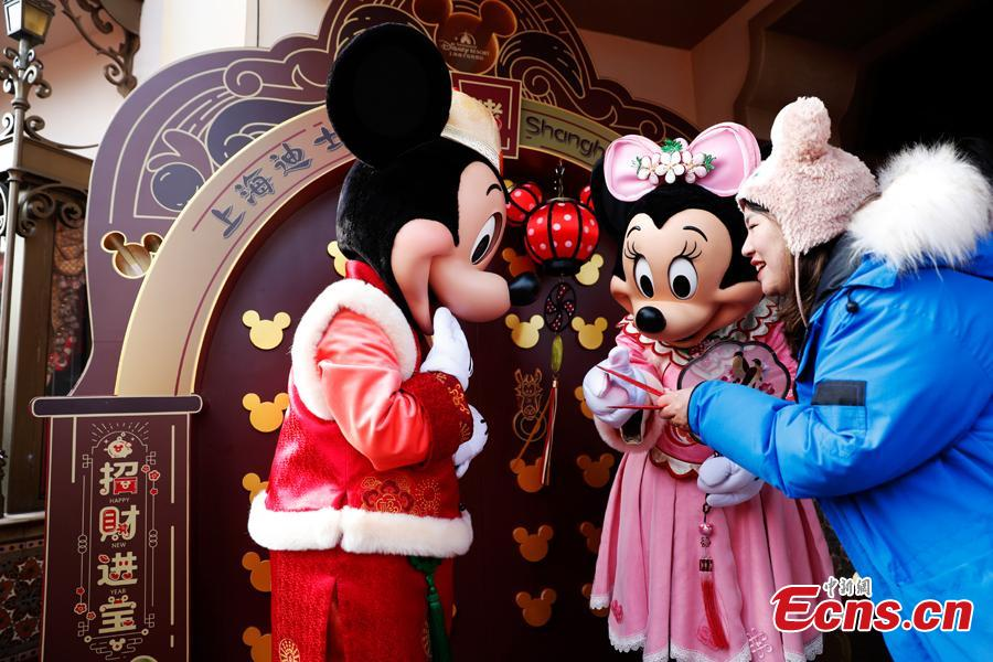 A tourist plays with Mickey and Minnie in the Shanghai Disney Resort, Jan. 1, 2019.  The Shanghai Disney launched \