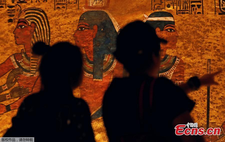 Visitors look at ancient Egyptian drawings on the newly renovated wall of boy pharaoh King Tutankhamun\'s tomb in Valley of the Kings in Luxor, Egypt January 31, 2019. A century after the tomb of Tutankhamun was discovered, revealing the mummified boy-king buried more than 3,000 years ago, it has re-opened, brighter and safer thanks to painstaking work to repair damage caused by dust, damp and visitors. (Photo/Agencies)