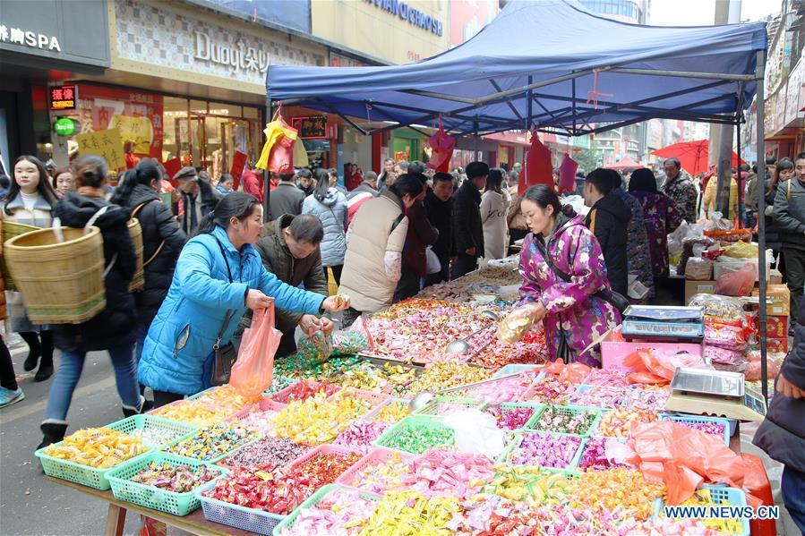 Customers buy candies at a local market in Yuping Dong Autonomous County of Tongren City, southwest China\'s Guizhou Province, Jan. 31, 2019. People are busy buying goods in Guizhou for the upcoming Spring Festival, which falls on Feb. 5 this year. (Xinhua/Liu Dejun)