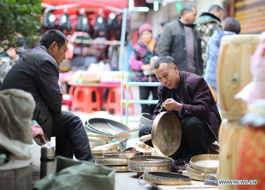 Customers select gongs, a traditional Chinese musical instrument, at a local market in Yuping Dong Autonomous County of Tongren City, southwest China\'s Guizhou Province, Jan. 31, 2019. People are busy buying goods in Guizhou for the upcoming Spring Festival, which falls on Feb. 5 this year. (Xinhua/Hu Panxue)