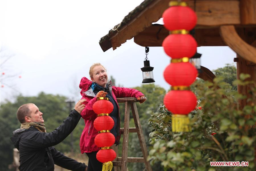 A British couple hang red lanterns for the upcoming Spring Festival at a hostel in Wulingyuan District of Zhangjiajie City, central China\'s Hunan Province, Jan. 31, 2019. The Spring Festival, or the Chinese Lunar New Year, falls on Feb. 5 this year. (Xinhua/Wu Yongbing)