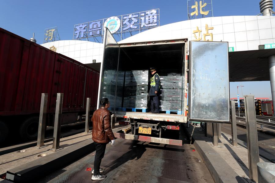 A vegetable transporter\'s vehicle undergoes inspection before entering Beijing. (Photo by WANG JING/CHINA DAILY)