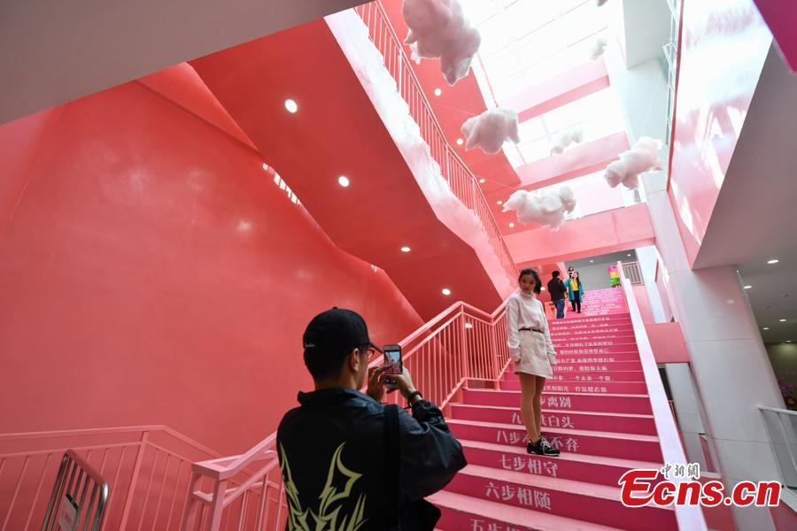 People take photos on pink stairs at the exit of Chunrong Street Subway Station in Kunming City, Southwest China's Yunnan Province. With cotton clouds suspended in the air and cute love quotes written on the stairs, the pink subway station has quickly gained widespread traction among young people. (Photo: China News Service/Ren Dong)