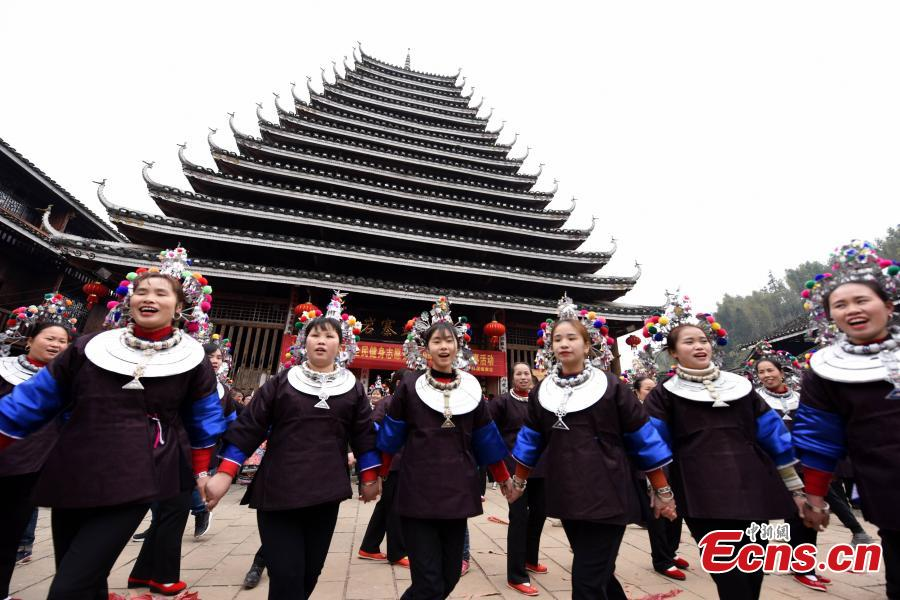 Nearly 200 women of the Dong ethnic group attend a group activity that shows the traditional custom of outmarried women going back to the home of their parents, often donning grand costumes and carrying gifts, in Pingyan Village, Sanjiang Dong Autonomous County, Guangxi Zhuang Autonomous Region, Feb. 1, 2019. The custom has become a draw that attracts tourists. (Photo: China News Service/Gong Pukang)