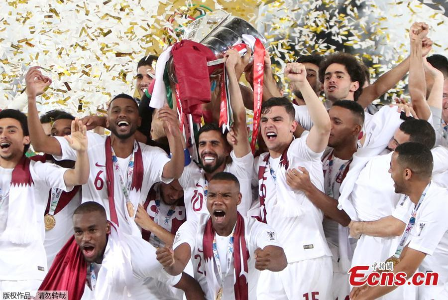 Qatar\'s Abdelaziz Hatim and team mates celebrate winning the Asian Cup with the trophy in Abu Dhabi, United Arab Emirates, February 1, 2019. Qatar stunned four-time champion Japan 3-1 to win the AFC Asian Cup for the first time as striker Almoez Ali scored his record-breaking ninth goal in the tournament on Friday. (Photo/Agencies)