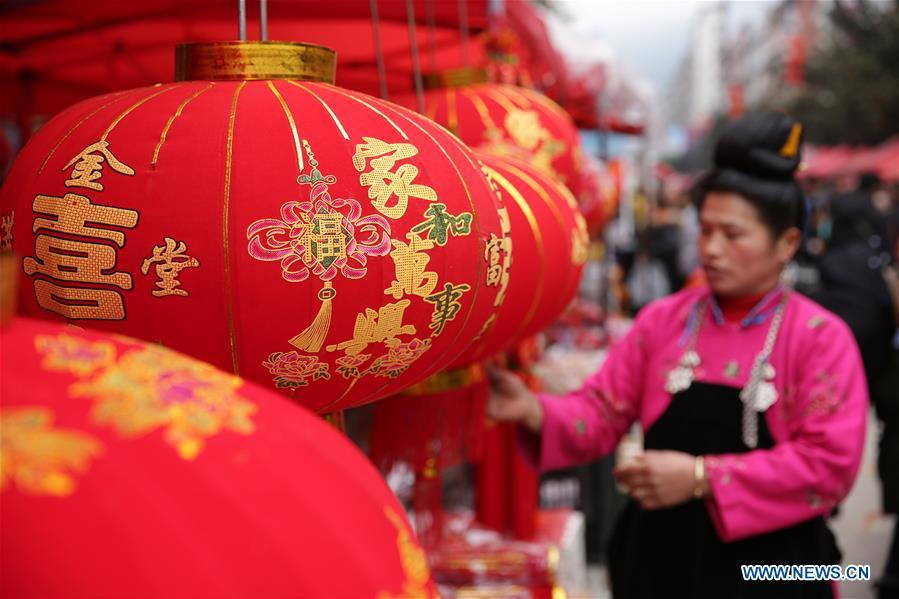 A woman selects red lanterns at a local market in Danzhai County, southwest China\'s Guizhou Province, Jan. 31, 2019. People are busy buying goods in Guizhou for the upcoming Spring Festival, which falls on Feb. 5 this year. (Xinhua/Huang Xiaohai)