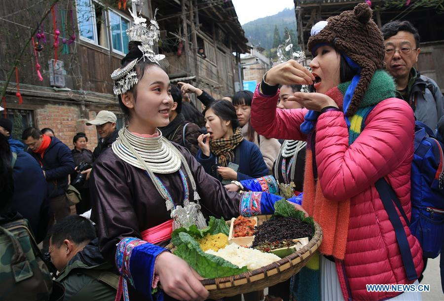 Tourists taste traditional food of Dong ethnic group during the Spring Festival holiday in Dingdong Village of Qiandongnan Miao and Dong Autonomous Prefecture, southwest China\'s Guizhou Province, Feb. 8, 2019. (Xinhua/Long Tao)