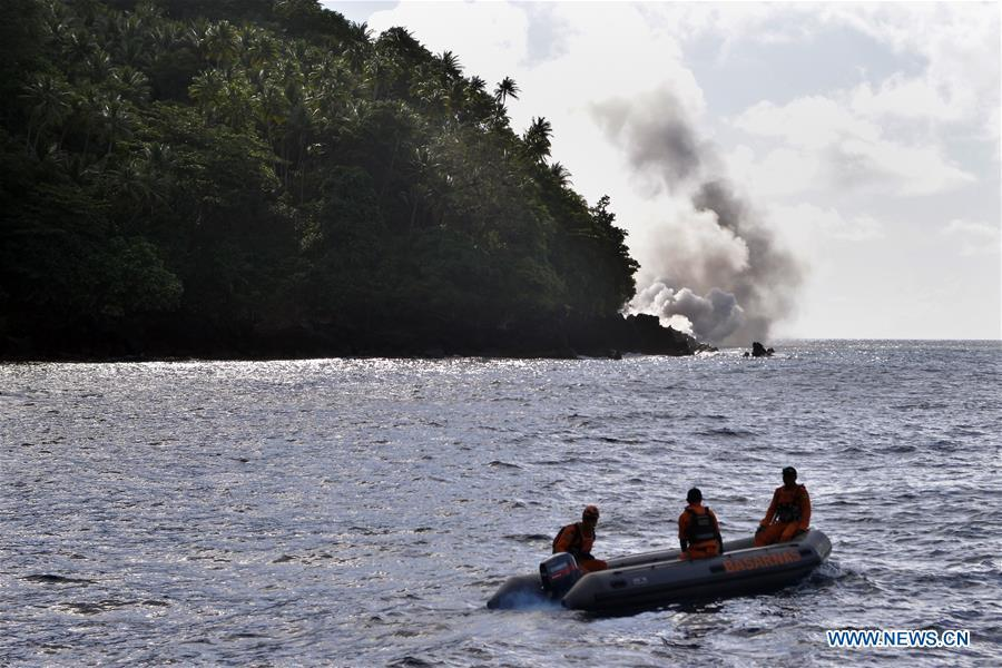 Search and Rescue (SAR) team members row a boat as they watch the lava lane of Mount Karangetang in the background in North Sulawesi, Indonesia, Feb. 10, 2019. Hot lava and volcanic materials that spewed from Mount Karangetang volcano in Indonesia\'s North Sulawesi province cut roads and buried bridges, while bad weather hampered evacuation operations, officials said on Saturday. Local authorities were trying to evacuate 508 villagers from the area. (Xinhua/Stringer)