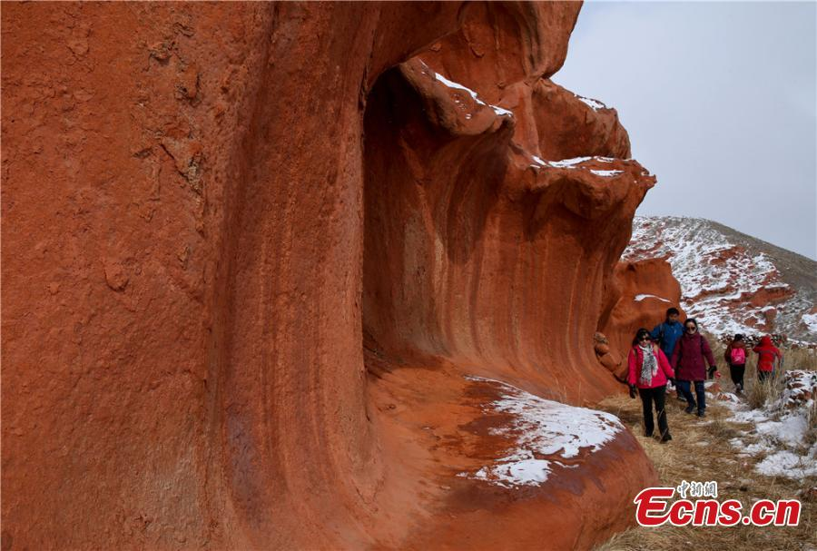 Tourists visit the snow-covered Danxia landform in Sunan Yugur Autonomous County, Northwest China\'s Gansu Province during the Spring Festival holiday. The Danxia landform is a unique type of geomorphology formed from red-colored sandstone and characterized by steep cliffs. (Photo: China News Service/Wang Jiang)