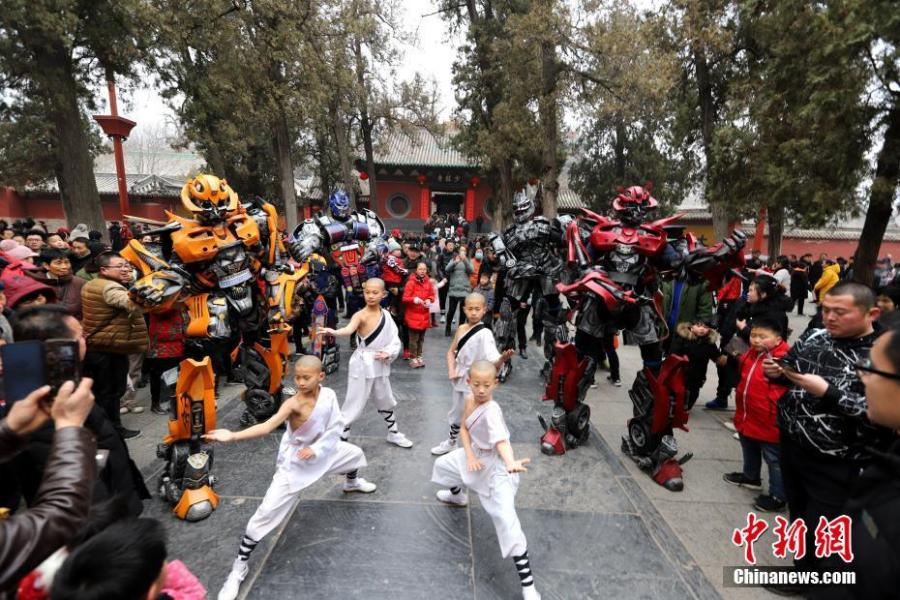 Students of kung fu at Shaolin Temple pose with Transformer-like statues in Dengfeng City, Central China\'s Henan Province, Feb. 7, 2019, as many tourists visit the famed Buddhist temple during the Lunar New Year holiday. (Photo: China News Service/Wang Zhongju)