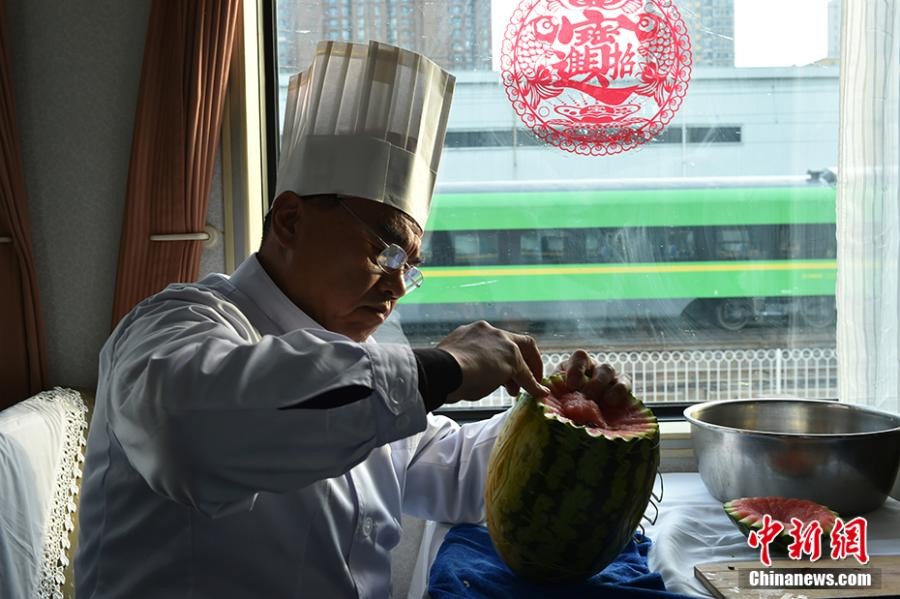 Wang Jinliang carves a watermelon on a train in Beijing during Spring Festival, China\'s Lunar New Year. Wang, 59, has worked on trains for more than 40 years, starting as a cook in 1978 before moving to roles as chef, kitchen head and now Party chief of the passengers service department. As the 2019 Spring Festival was his last one on duty, he spent 80 yuan ($12) buying fruits and vegetables including watermelon, carrot and Chinese cabbage to show his carving creations. Wang also said his skill in making fancy food garnishes enabled him to contribute to marking important occasions in his job, such as the first train from Beijing to Shenzhen in 1996. (Photo: China News Service/Zhai Lu)