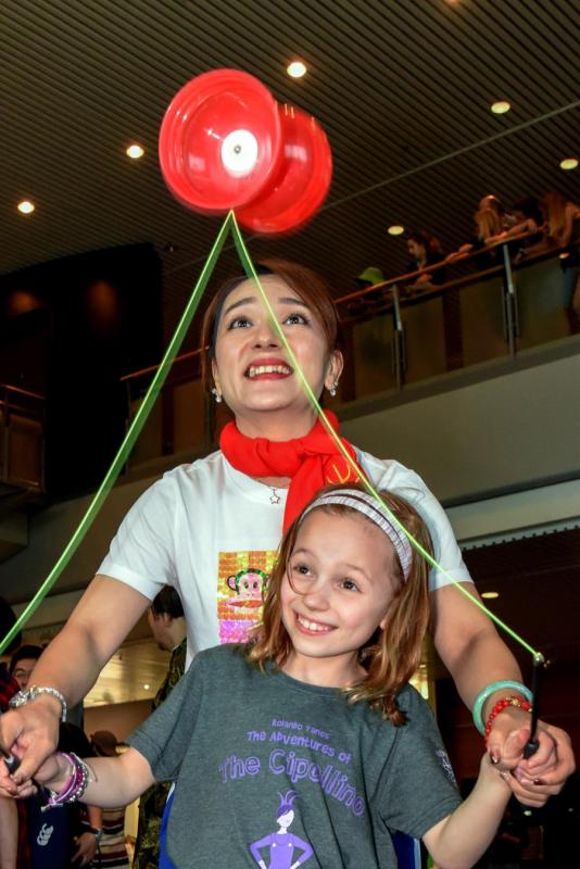 An actress of the Jinan Acrobatic Troupe plays the diabolo with a local girl at the Museum of New Zealand Te Papa Tongarewa in Wellington on Saturday.  (PHOTO/XINHUA)