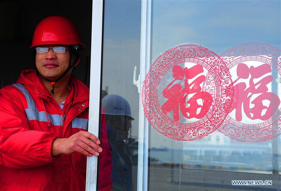 Gong Fuqiang, a crane driver, looks out of the door of a rest room at Zhenghe Xinggang Terminals of Taicang Port in Suzhou, east China\'s Jiangsu Province, Feb. 11, 2019, the first workday after Spring Festival holiday. (Xinhua/Ji Haixin)