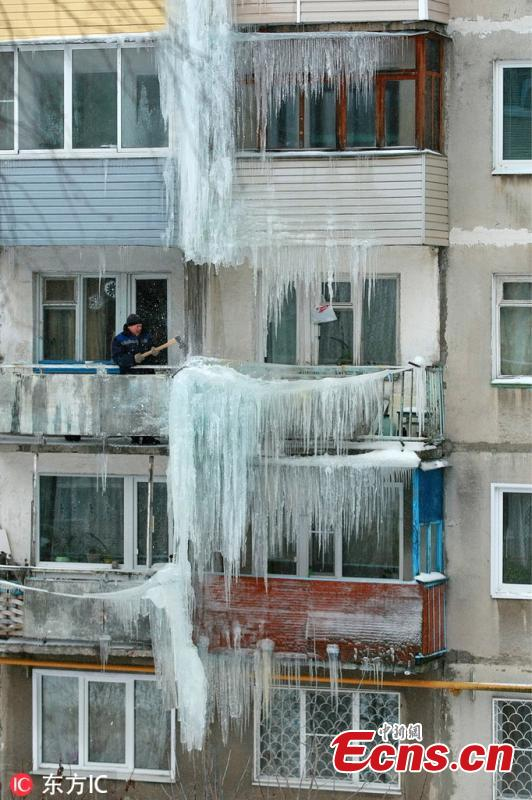 A man moves ice on a residential building in Ivanovo, Russia, Feb. 11, 2019. (Photo/IC)