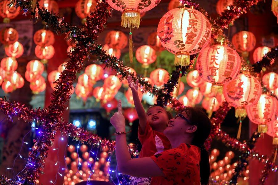 A mother holds her daughter and admires lanterns, celebrating Lunar New Year on the outskirts of Bangkok on Feb. 5. (PHOTO/XINHUA)
