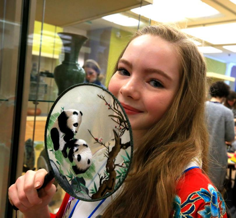 A visitor shows off a Chinese moon-shaped fan at the National Art Museum of the Republic of Belarus in Minsk on Saturday. (PHOTO/XINHUA)