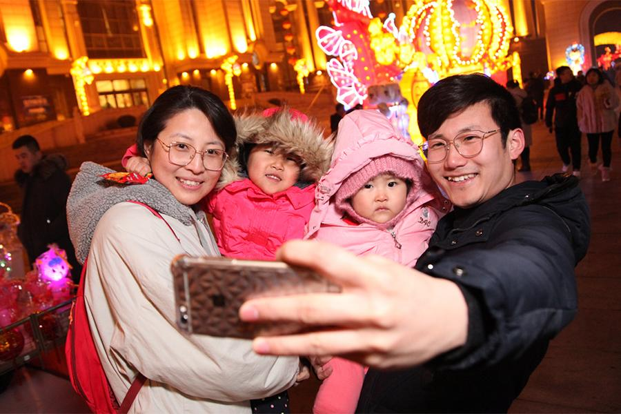 A family of four takes a photo in front of lanterns during the Tourism and Cultural Festival and Lantern Festival in Jinshitan. (Photo by Ma Wenjun/For chinadaily.com.cn)