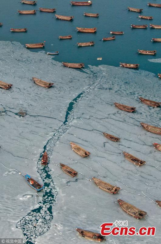 Boats are stranded in frozen sea at a port in Dalian City, Northeast China\'s Liaoning Province amid a cold front. A fisherman had to break ice to transport supplies to a marine fish culture zone. (Photo/VCG)