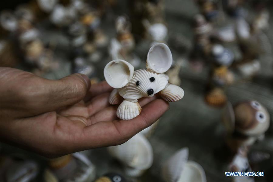 Palestinian young man Ahmed al-Madhoun, 31, displays an art piece he made with seashells at his house in Gaza City, on Feb. 10, 2019. A Palestinian young man from Gaza turns seashells into beautiful artifacts that adorn his home to satisfy his passion for this type of art. Using seashells he collects from Gaza beaches, 31-year-old Ahmed al-Madhoun makes various art pieces such as animals, birds and some funny characters. Al-Madhoun, who holds a college degree in radio and television engineering and works for a local telecommunication company, has been collecting multiple forms of seashells from the Gaza seashore for more than four years. The young man began the hobby of seashell art about a year and a half ago, and he already made large numbers of art pieces.  (Xinhua/Stringer)
