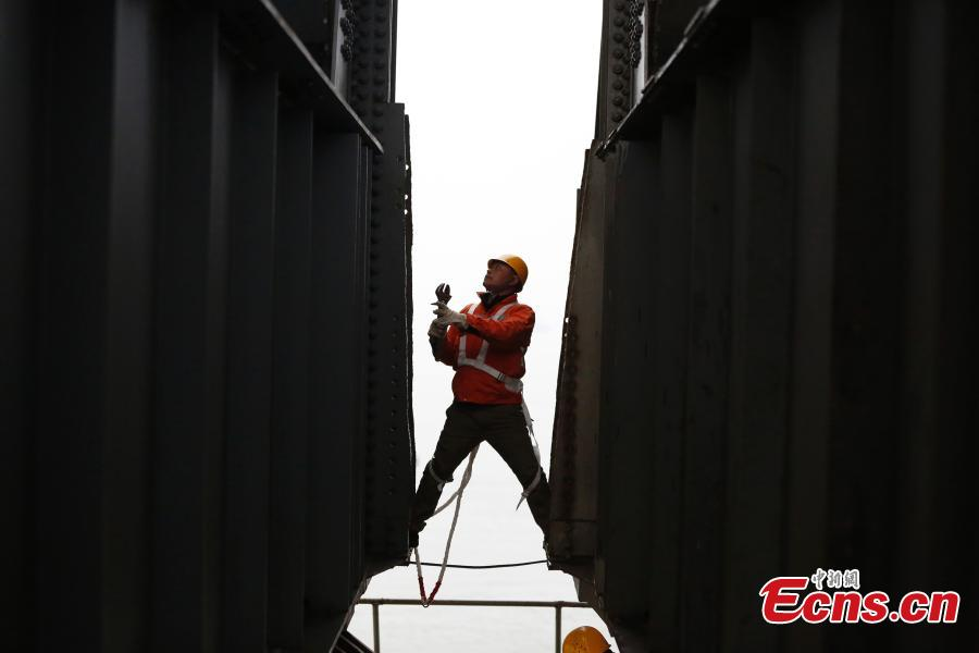 A technician conducts a routine safety check on the Jiujiang Yangtze River Bridge, a major connection of the Beijing-Kowloon Railway in Jiujiang City, East China\'s Jiangxi Province during the travel peak of the Spring Festival. Despite the wind and vibration caused by the passing trains, they continued working in baskets hung under the bridge\'s girder, about 20 meters above the rolling Yangtze River. (Photo: China News Service/Ding Bo)